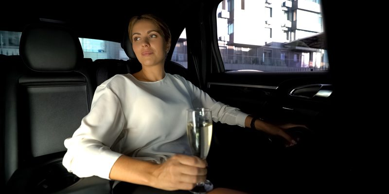 Woman drinking champagne on car backseat